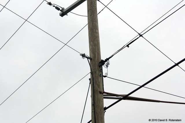 Eruv boundary: borrowed pole and wires. The vertical black strips are the attached lechi. Photograph by David Rotenstein, October 2010.