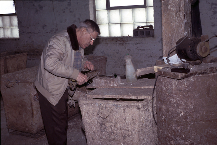 Frank Hayson sharpens shears that he used to trim wool from pelts that would not come free by hand. Photo by author.
