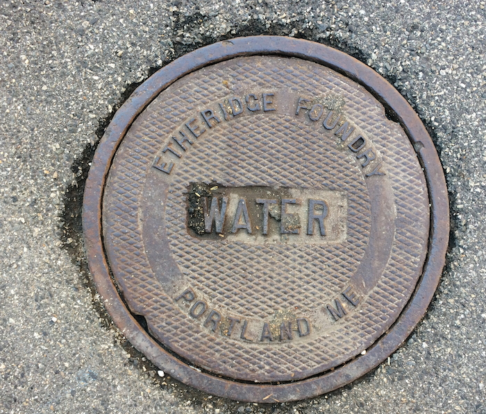 Portland has a rich industrial history. Smith's shop is connected to it through several strands, including an Etheridge Foundry cart in his shop. The Etheridge Foundry fabricated many of Portland's manhole covers, like this one on one of the city's wharves.