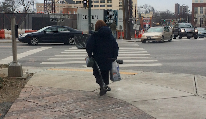 A woman carrying two snow shovels and ice melter walks along Fenton Street in Silver Spring, Md.