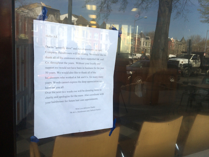 Letter posted in the window of Jak & Co., April 2015. Reflected in the window are turn of the century homes being rehabilitated for new waves of residents.